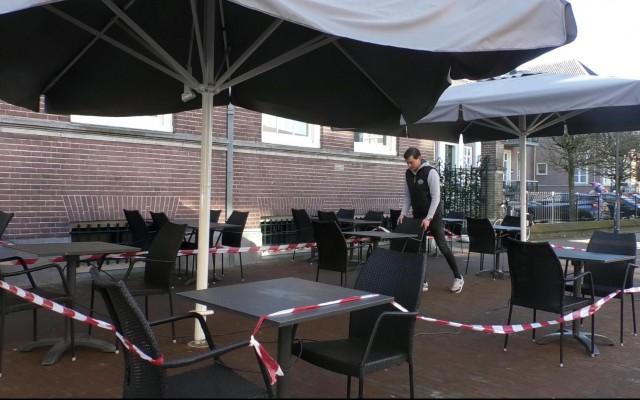 Medewerker van Grand Café Ledeboer bezig met terras inrichten