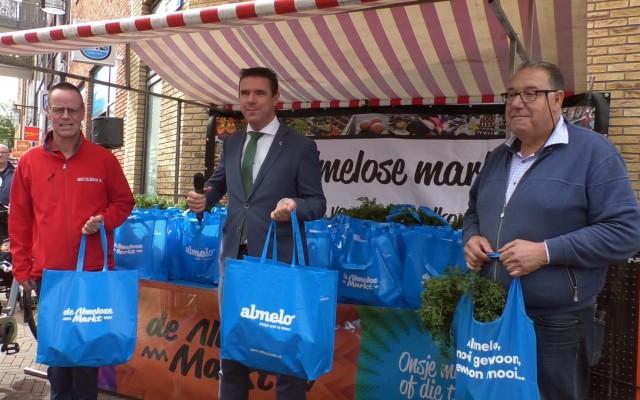 Wethouder Eugène deelt duurzame tassen uit.